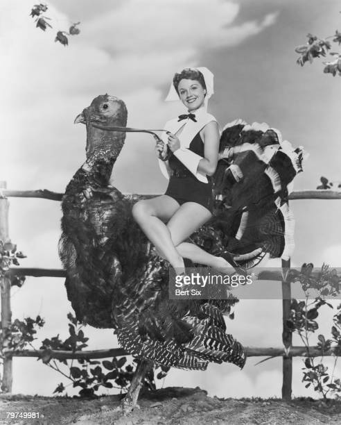 American actress Virginia Gibson in a glamorous version of puritan costume rides a giant Turkey circa 1952