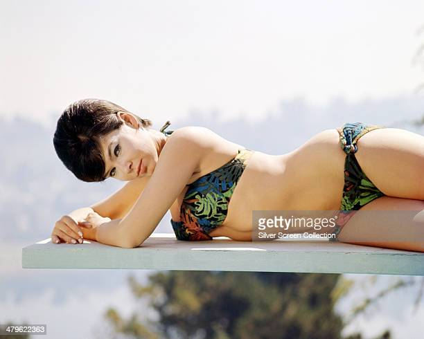 American actress Yvonne Craig wearing a bikini and lying on a diving board circa 1965