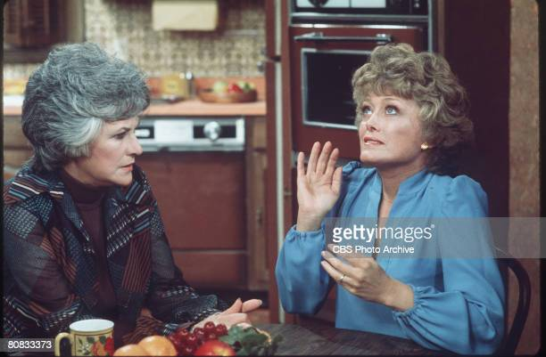 American actresses Beatrice Arthur and Rue McClanahan talk at a table in a scene from the television show 'Maude,' Los Angeles, California, mid 1970s.