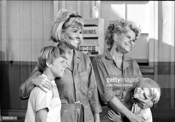 American actresses Doris Day as Doris Martin and Rose Marie as Myrna Gibbons with their faces dirty from grease and wearing mechanics' jumpsuits hug...