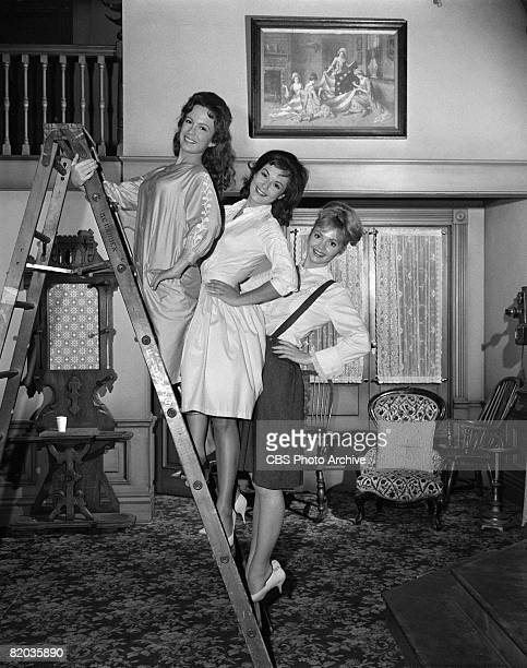 American actresses from left Linda Henning Pat Woodell and Jeannine Riley pose together on different rungs of a stepladder on the set of 'Petticoat...