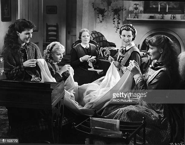 American actresses Jean Parker Joan Bennett Spring Byington Frances Dee and Katharine Hepburn sew in character on set as the March women in a still...