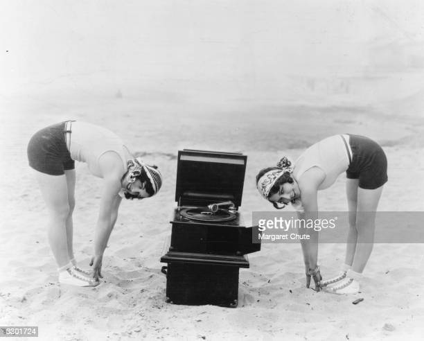 American actresses Joan Crawford and Dorothy Sebastian practise reducing exercises on Santa Monica beach California as they listen to music from a...