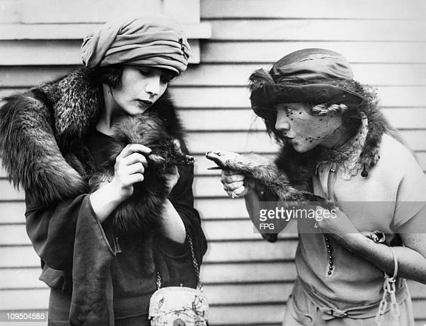 American actresses Kathleen Clifford and Betty Compson stage a mock fight with their fur stoles circa 1920