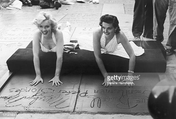 American actresses Marilyn Monroe and Jane Russell lie on their stomachs and press their hand prints in wet cement as they promote their film...