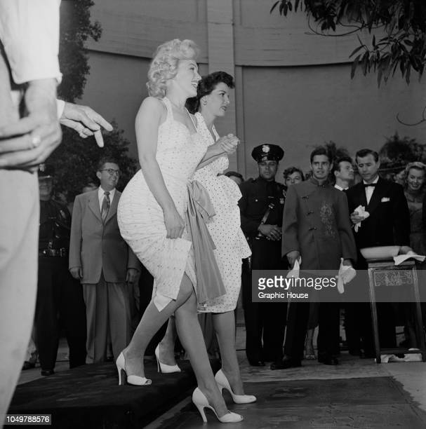 American actresses Marilyn Monroe and Jane Russell make imprints of their feet in wet cement in a joint handprint ceremony at Grauman's Chinese...