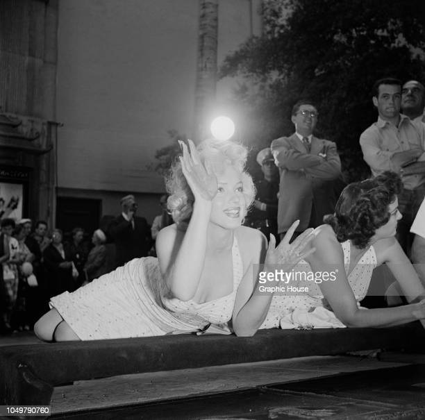American actresses Marilyn Monroe and Jane Russell make imprints of their hands in wet cement in a joint handprint ceremony at Grauman's Chinese...