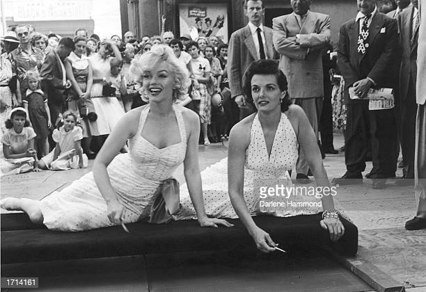 American actresses Marilyn Monroe and Jane Russell sit on a cushion and prepare to sign their foot and hand prints in the cement in front of...