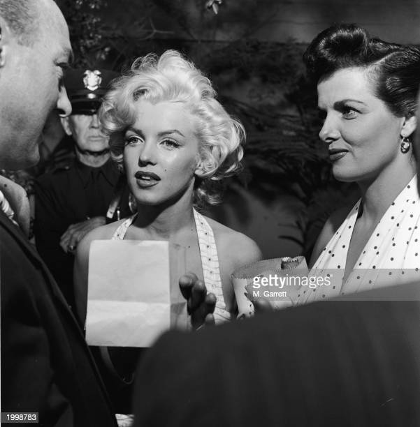 American actresses Marilyn Monroe and Jane Russell speak to an unidentified man as they promote director Howard Hawks' film 'Gentlemen Prefer...