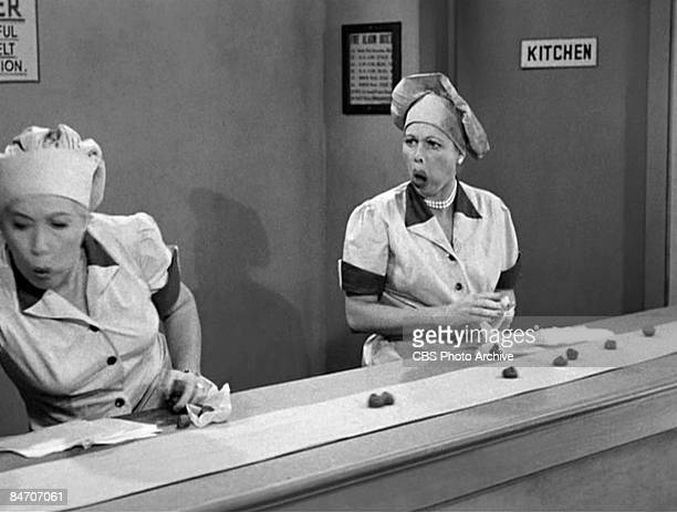 American actresses Vivian Vance as Ethel Mertz and Lucille Ball as Lucy Ricardo work sideby side at a candy factory conveyor belt in an episode of...