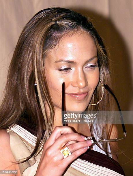 American actresssinger Jennifer Lopez takes off her sunglasses during a photo session prior to her press conference at a Tokyo hotel 16 February 2001...