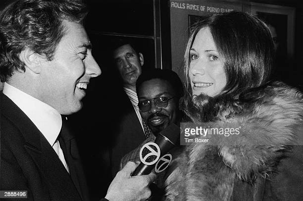American adult film actor Marilyn Chambers is interviewed by reporter Kevin Sanders as she attends the premiere of the film 'Resurrection of Eve' New...