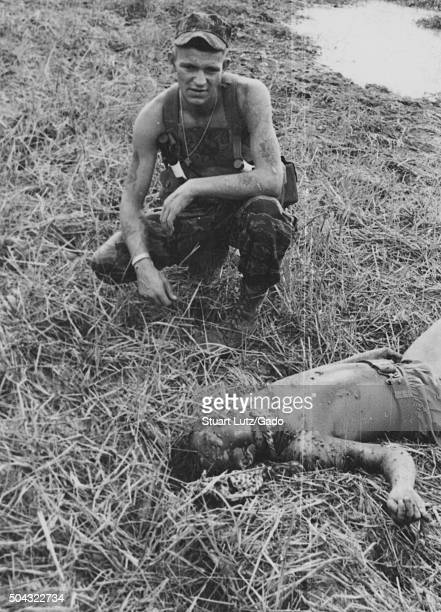American advisor in uniform in Vietnam kneeling over the mutilated body of a dead Viet Cong soldier laid on a grassy field early in the Vietnam War...