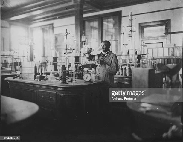 American agricultural chemist and educator Dr George Washington Carver works in a laboratory 1910s