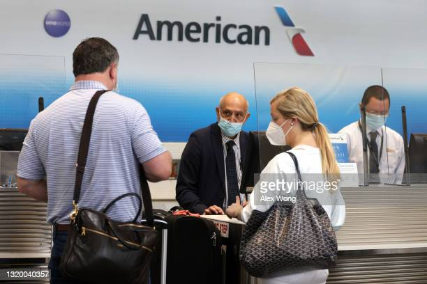 American Airlines agents help passengers to check in their flights at Ronald Reagan Washington National Airport May 25, 2021 in Arlington, Virginia....