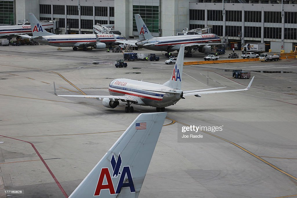 American Airlines aircraft sit on the tarmac at Miami International Airport as Miami-Dade County Mayor Carlos A. Gimenez, and Airport Aviation Director Emilio T. González, hold a press conference regarding the U.S. Justice Department and state attorneys general suit against the American Airlines and US Airways merger on August 21, 2013 in Miami, Florida. The Mayor and aviation director addressed the letter they sent Attorney General Eric H. Holder, Jr. in which they stated their concerns with the review of the merger due to the damage it will do to the local economy if the merger isn't allowed to go through.