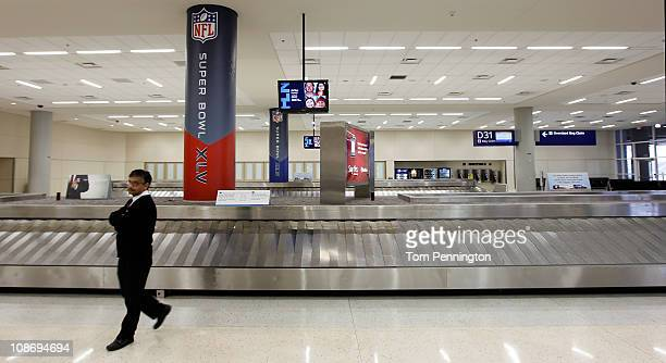 American Airlines baggage agent Roger Rajan stands in an empty baggage claim area in Terminal D after hundreds of flights were canceled at DFW...