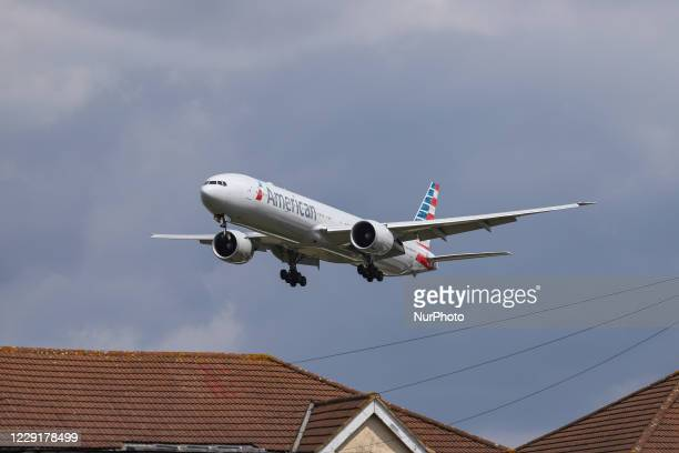 American Airlines Boing 777-300 wide-body aircraft as seen on final approach over the houses of Myrtle Ave, for landing at London Heathrow LHR EGLL...
