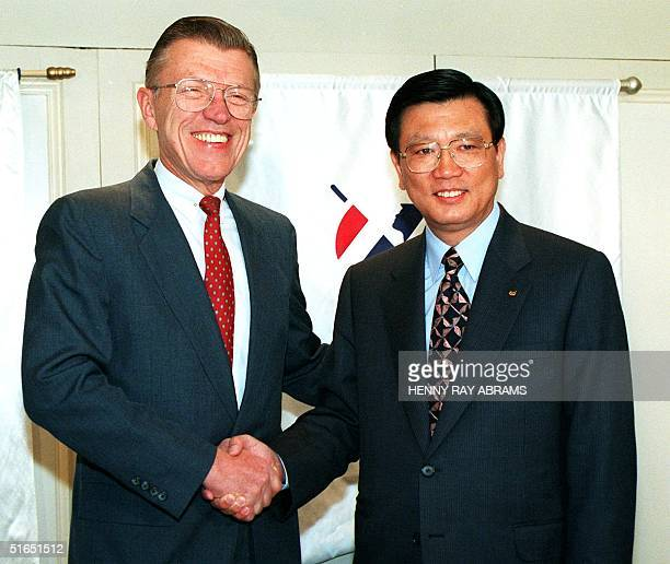 American Airlines Chairman and Chief Executive Officer Robert Crandall shakes hands with Asiana Airlines President and Chief Executive Officer Sam...
