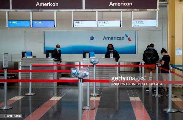 American Airlines employees check in two passengers at a mostly empty checkin counter in Ronald Reagan Washington National Airport in Arlington...