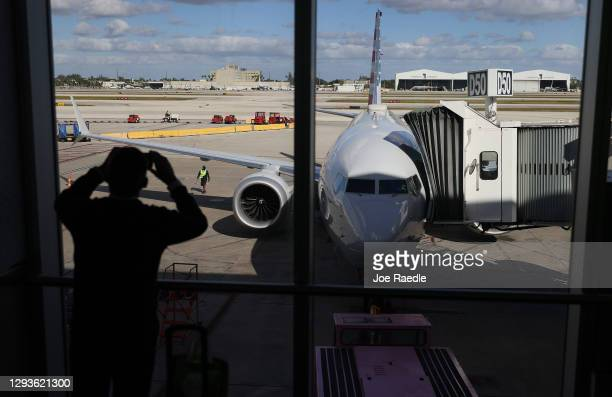 American Airlines flight 718, a Boeing 737 Max, is seen parked at its gate at Miami International Airport as passengers board for the flight to New...