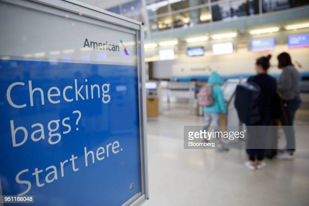 American Airlines Group Inc signage is displayed as travelers checkin for flights at DallasFort Worth International Airport in Grapevine Texas US on...