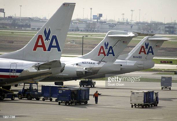 American Airlines jets sit on the tarmac as an American Eagle jet taxis to the gate at O'Hare International Airport April 25 2003 in Chicago A...