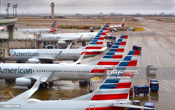 American Airlines passenger jets parked at their gates on a rainy morning at Dallas/Fort Worth International Airport which serves the Dallas/Fort...