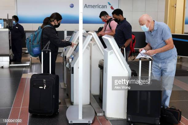 American Airlines passengers check themselves into their flights through self-service kiosks at Ronald Reagan Washington National Airport May 25,...