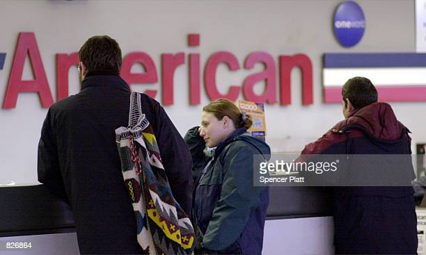 American Airlines passengers wait by the counter to pick up their tickets March 2 2001 at John F Kennedy International airport in New York City A...