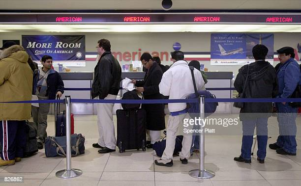 American Airlines passengers wait in line by the counter to pick up their tickets March 2 2001 at John F Kennedy International airport in New York...