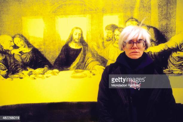 American all-round artist Andy Warhol, icon of the Pop Art Movement, posing seriously in front of The Last Supper, a personal interpretation the...
