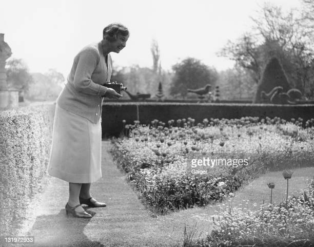 American amateur golfer Marion Hollins a member of the American women's golf team films the gardens at Great Fosters in Egham Surrey during a visit...