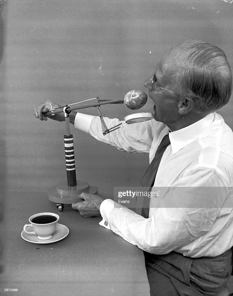 American amateur inventor Russel E Oakes demonstrates his doughnut dunker which prevents doughnuts dripping and wetting diner's fingers.