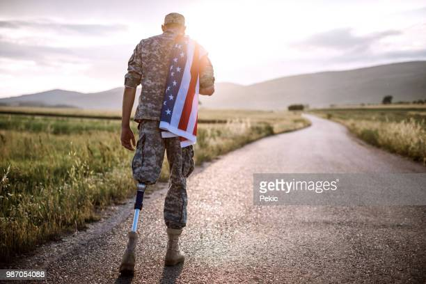 american amputee soldier on road - army soldier stock photos and pictures