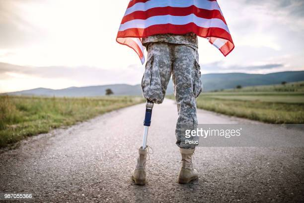 american amputee soldier on road - injured soldier stock photos and pictures