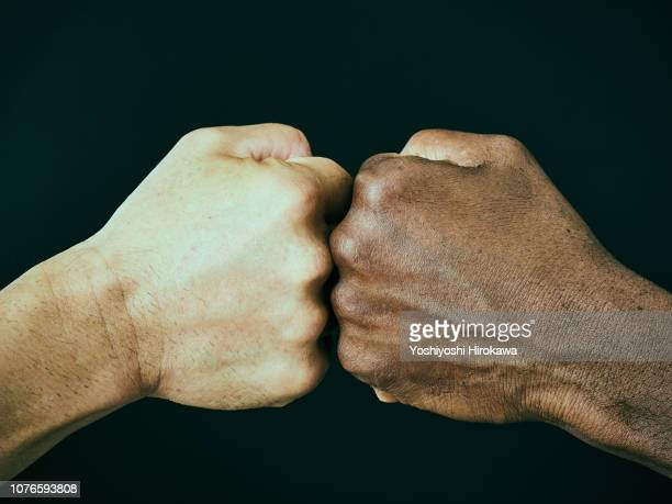 american and a japanese bumping fists - multiculturalism stock pictures, royalty-free photos & images