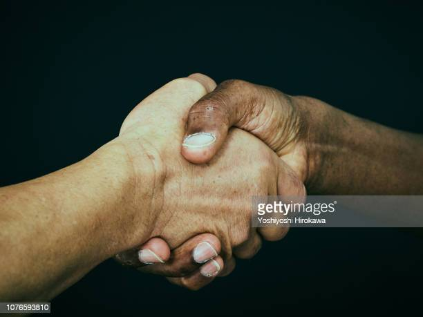 american and a japanese shaking hand - handshake stock pictures, royalty-free photos & images
