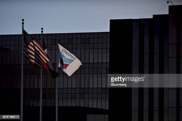 American and Chevron Corp flags fly outside an office building in Midland Texas US on Thursday March 1 2018 Chevron the world's thirdlargest publicly...