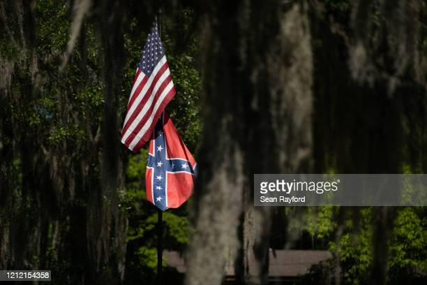 American and Confederate flags fly at a residence in the Fancy Bluff neighborhood on May 7, 2020 where Ahmaud Arbery lived in Brunswick, Georgia....