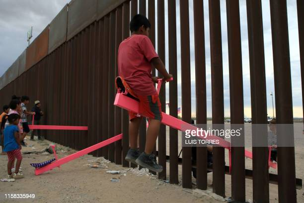 TOPSHOT American and Mexican families play with a toy called up and down over the Mexican border with US at the Anapra zone in Ciudad Juarez...