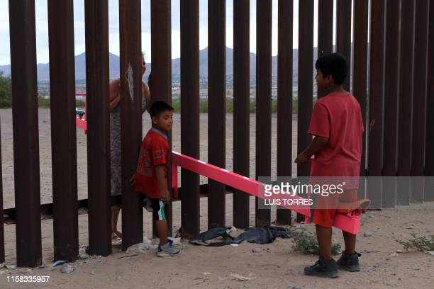 American and Mexican families play with a toy called up and down over the Mexican border with US at the Anapra zone in Ciudad Juarez Chihuahua State...