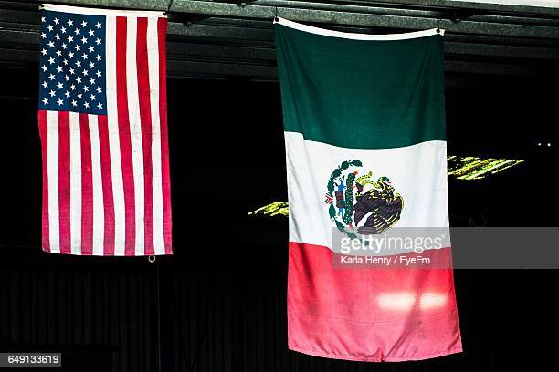 american and mexican flag hanging on roof - bandera mexicana fotografías e imágenes de stock