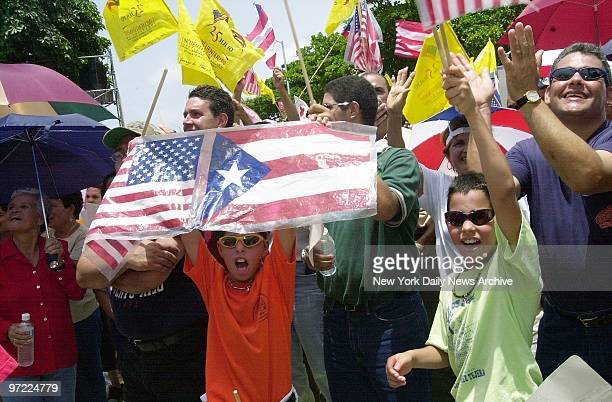 American and Puerto Rican flags are displayed by celebrators at a ceremony outside the Captiol Building in San Juan marking the 50th anniversary of...