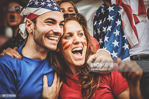 american and spanish supporter at the soccer stadium - rivaliteit stockfoto's en -beelden