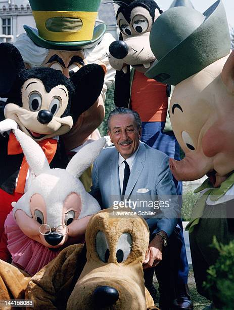 American animator and film director Walt Disney poses with actors costumed as some of his company's famous creations Anaheim California November 1964...