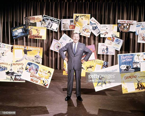 American animator and film producer Walt Disney with posters from some of his films circa 1955