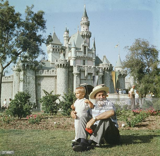 American animator and film studio founder Walt Disney sits on a grassy lawn with his grandson in front of the Magic Kingdom's castle at Disneyland...