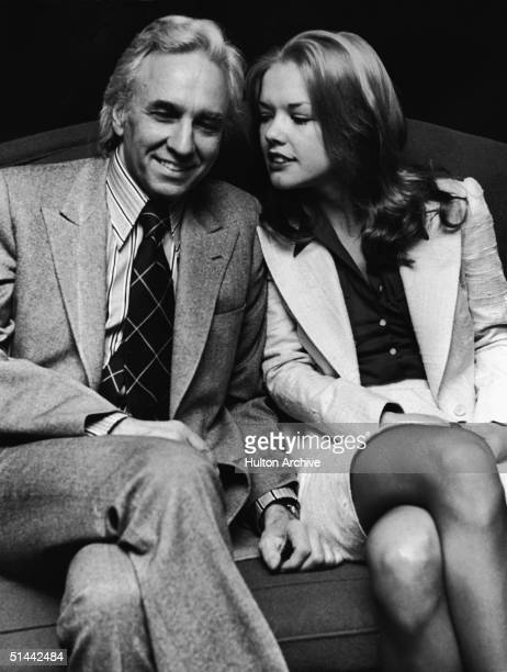 American AP supermarket chain heir and art collector Huntington Hartford sits on a couch with his soontobe fourth wife model Elaine Kay as they wear...
