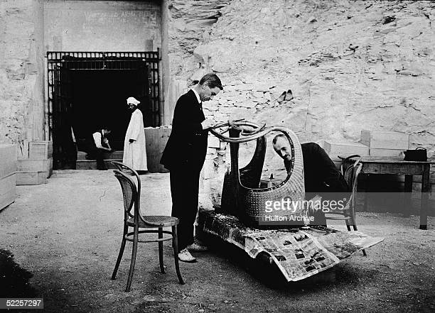 American archaeologist Arthur Mace of the Metropolitan Museum and British chemist Alfred Lucas with the Egyptian government inspect a chariot from...
